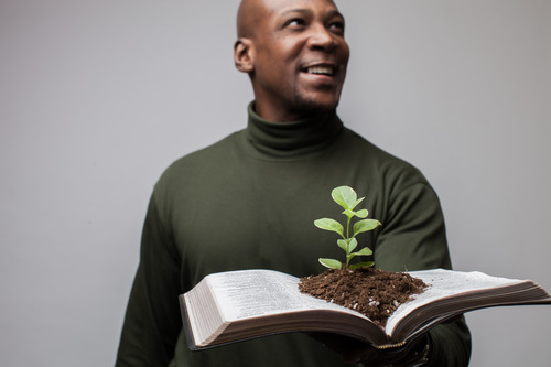 man with plant growing from open bible
