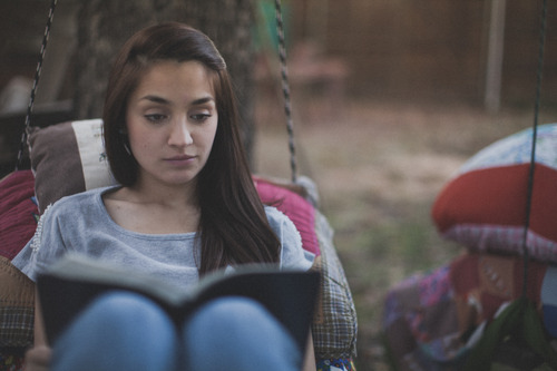 Girl on a swing reading bible